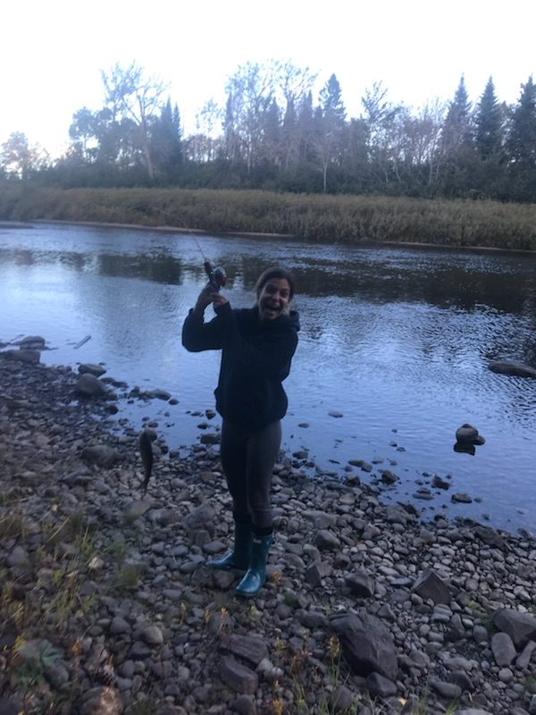 An excited woman holds up a fish she caught next to a river in Maine.