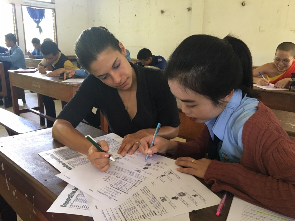 A female teacher helps a student with her English writing.