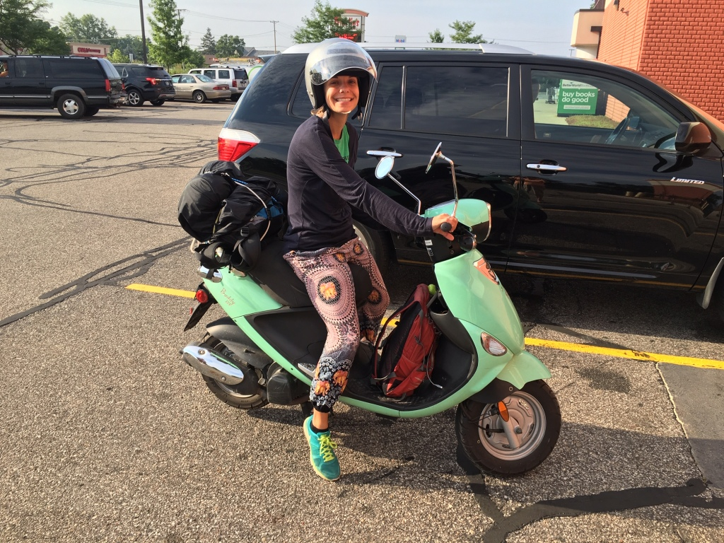 A smiling woman on a parked teal moped.