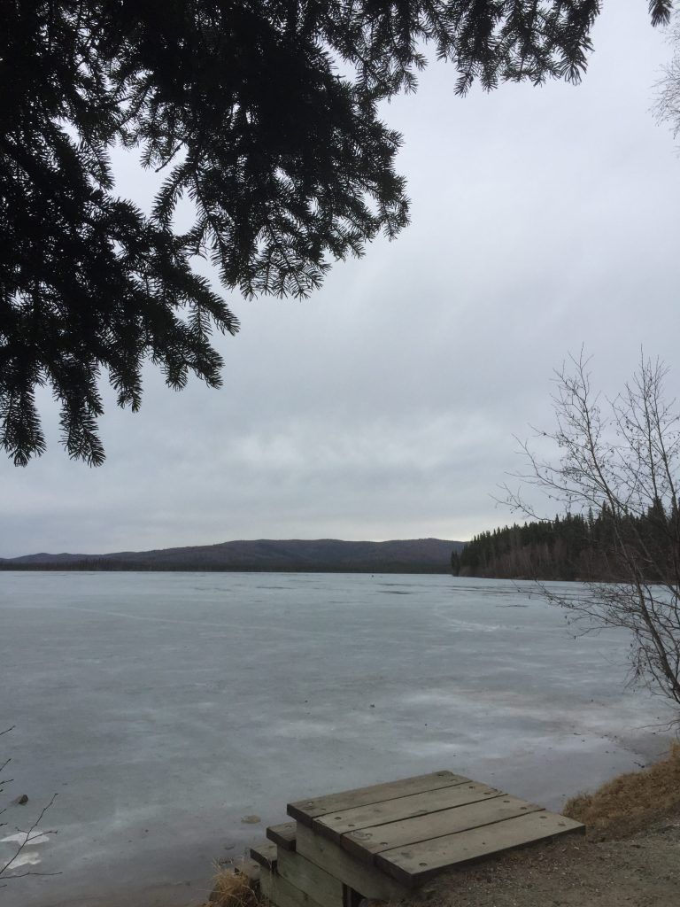 A grey sky over a mostly frozen lake.